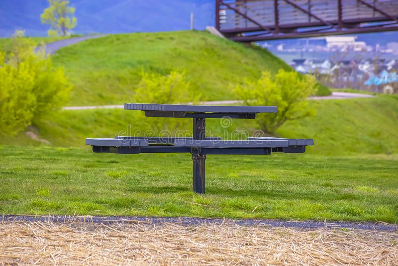 Ronde picknicklijst en zetels op een weelderig gebied naast een weg met bruine grassen royalty-vrije stock afbeeldingen