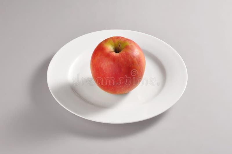 Ronde schotel met een rode appel royalty-vrije stock foto
