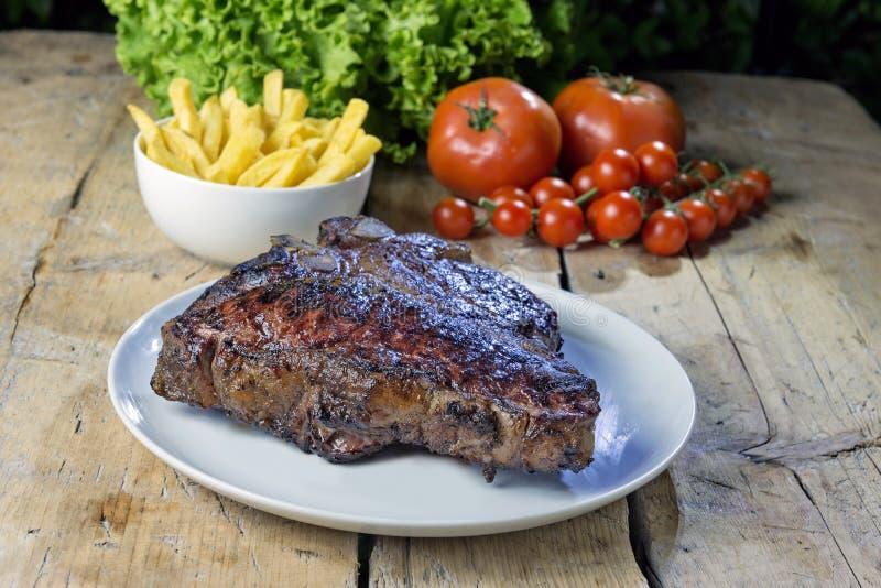 Ronde schotel met geroosterd porterhouse rundvleeslapje vlees op houten lijst royalty-vrije stock foto