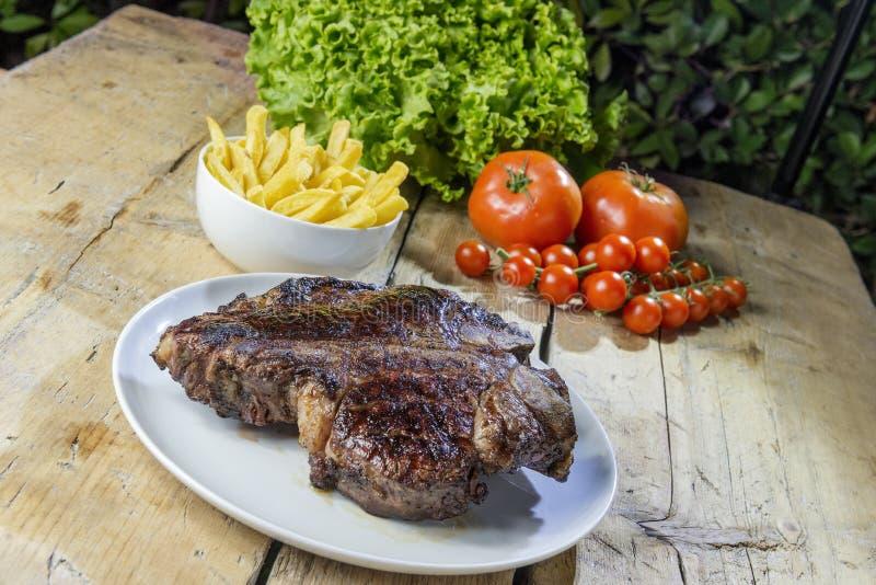 Ronde schotel met geroosterd porterhouse rundvleeslapje vlees op houten lijst stock afbeelding