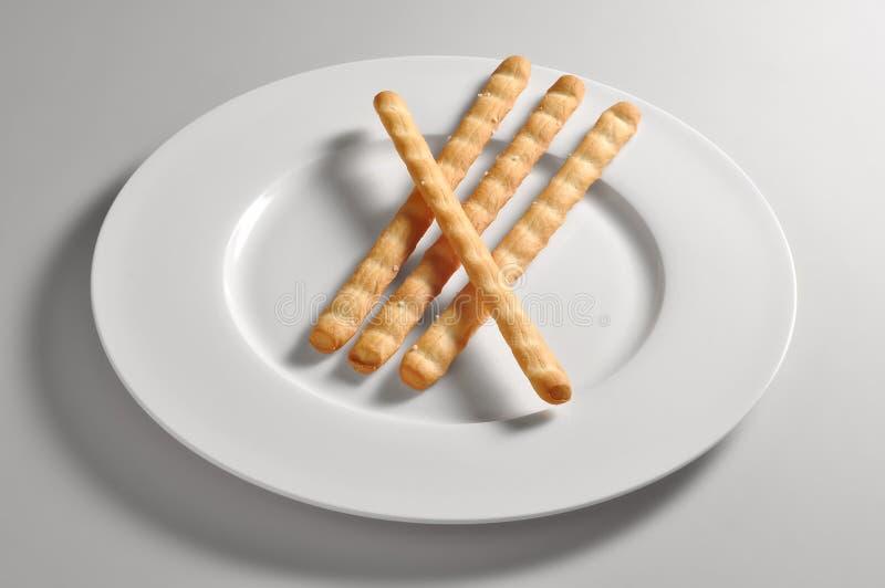 Ronde schotel met gezouten breadsticks stock foto's