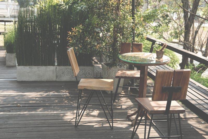 Rondetafel op terras van huis houten stoel op terras dichtbij tuin