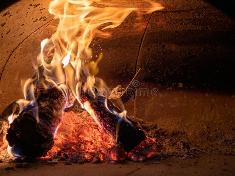 Rondins brûlants, cendres, et flammes intenses en four concret image libre de droits