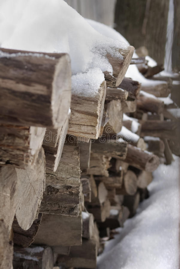 Rondins empilés de bois de chauffage couverts de neige - le jour d'hiver froid, préparent pour la cheminée photos stock