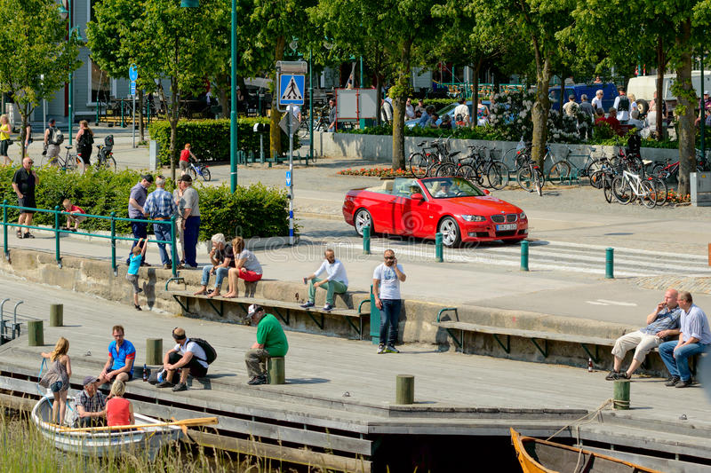 Ronneby city. Ronneby, Sweden - June 13, 2015: City life in Ronneby with lots of people enjoying the fine weather. One red car drive through stock photo