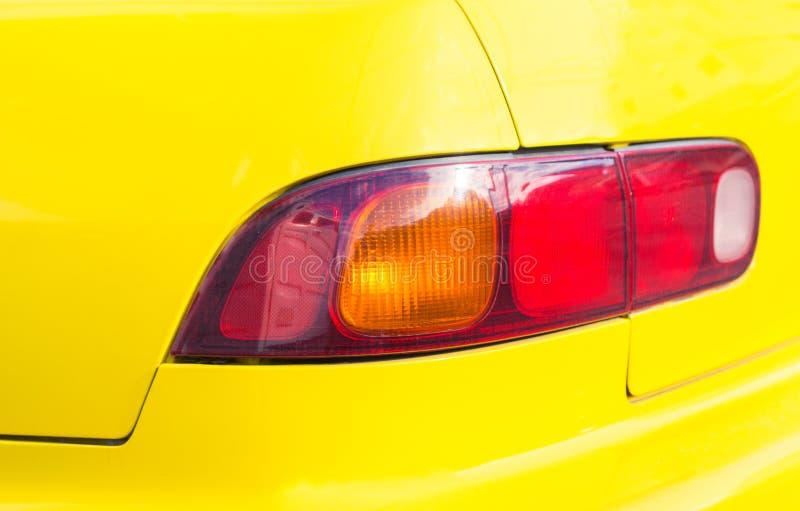 Rood achterlicht op gele auto Backlight van moderne sportwagen Vier wielenvervoer stock afbeelding