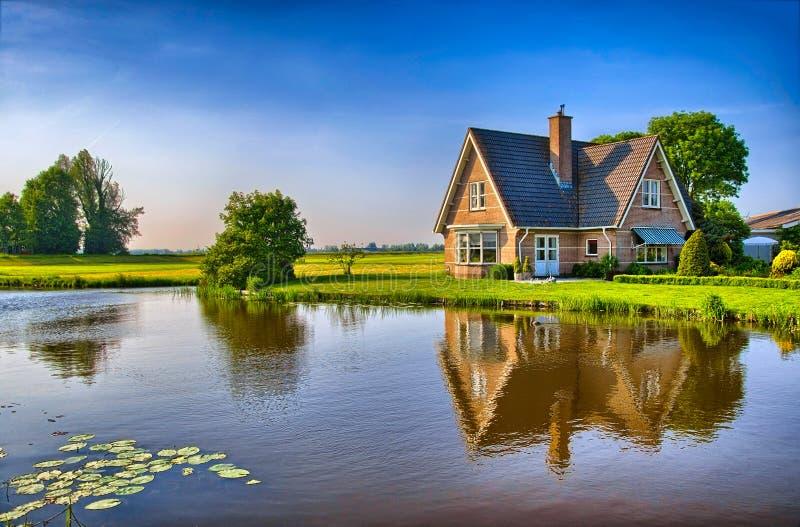 Rood bakstenenhuis in platteland dichtbij het meer met royalty-vrije stock foto's
