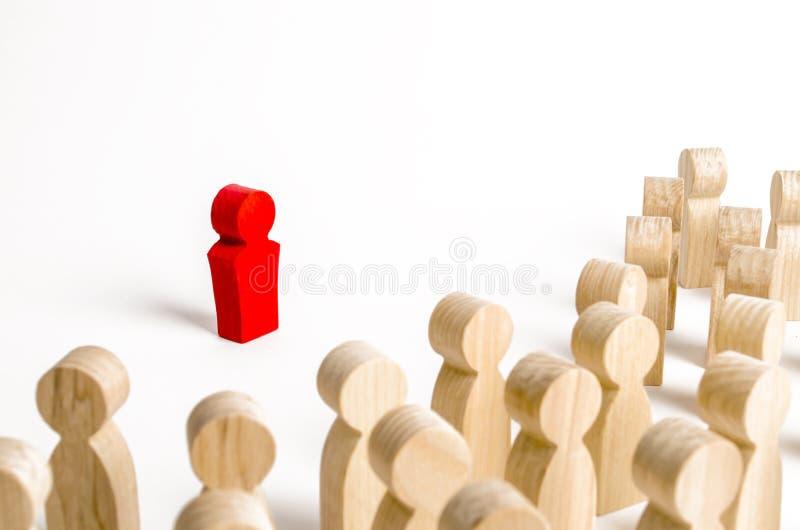 Rood beeldje van een mens in de schijnwerper van een menigte van mensen Leider, leiding en initiatiefnemer van actie het werk of  stock foto's