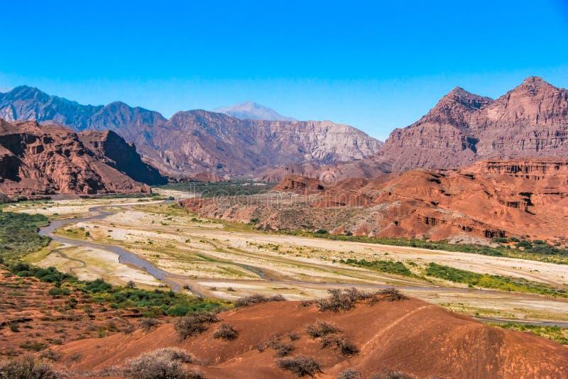 Rood bergenlandschap met een droge rivier onderaan de vallei stock fotografie