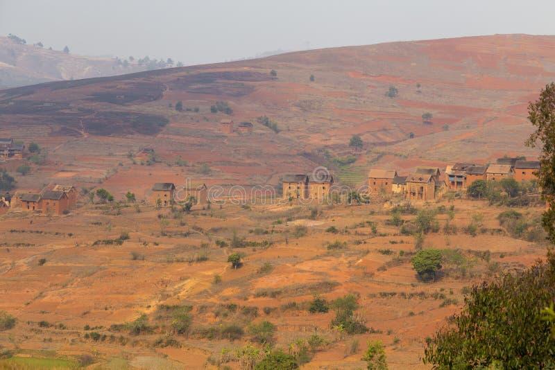 Rood berglandschap op een dorp van Madagascar stock afbeelding