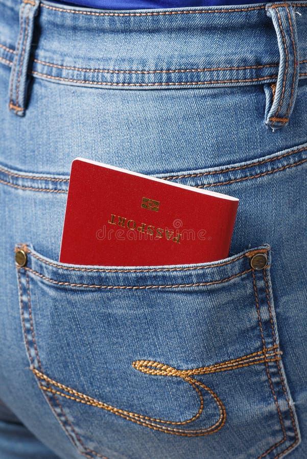 Rood biometrisch paspoort in het close-up van de jeanszak stock foto