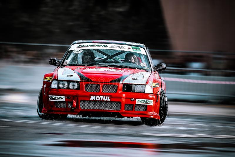 Rood BMW die op het natte asfalt afdrijven stock fotografie