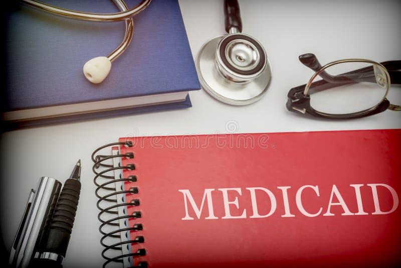 Rood boek met een adellijke titel medicaid samen met medische apparatuur stock foto