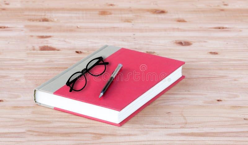 Rood boek met glazen en pen stock fotografie