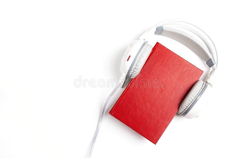 Rood boek met witte hoofdtelefoons op het op witte achtergrond AUD royalty-vrije stock foto