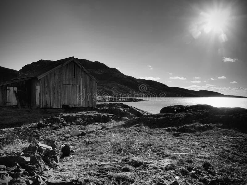 Rood botenhuis bij pijler, rotsachtig eiland, Noorwegen De traditionele rode witte bouw bij pijler dicht bij overzees stock afbeeldingen
