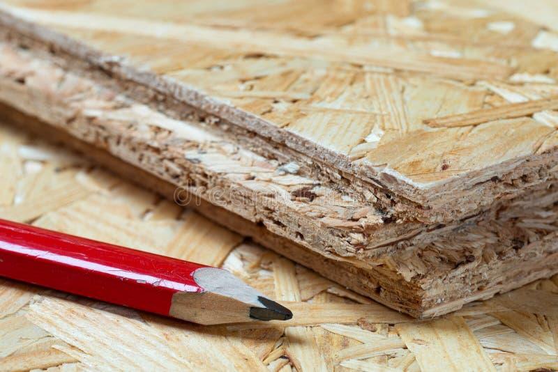 Rood carpenter potlood, naast de tongschar en de spaanplaat van de groef Blurale achtergrond royalty-vrije stock foto's