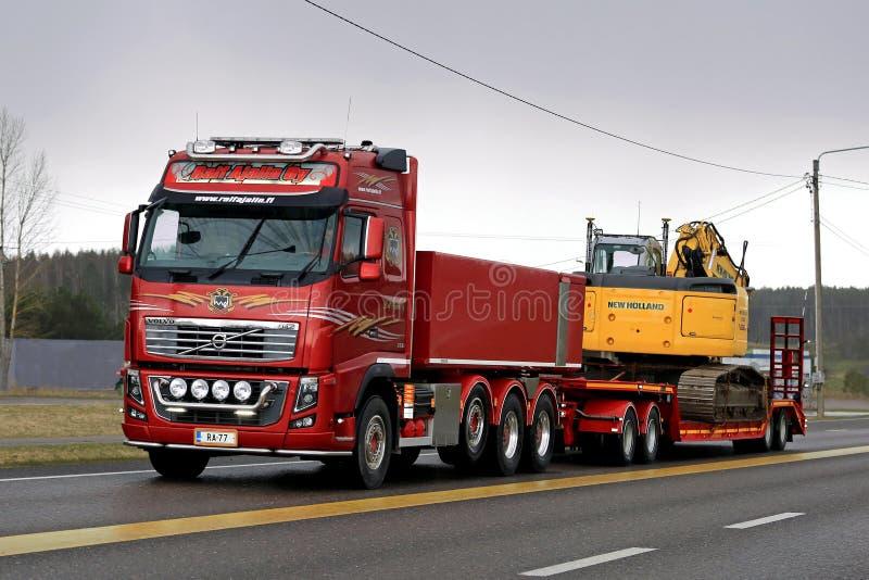 Rood de Transporten van Volvo FH16 750 Kruippakjegraafwerktuig in de Avond stock afbeelding
