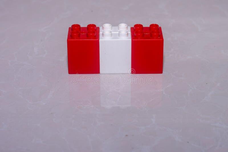 Rood, de witte vlag van Oostenrijk, en rood van stuk speelgoed blokken op een tegel met een bezinning en een ruimte wordt gemaakt stock foto