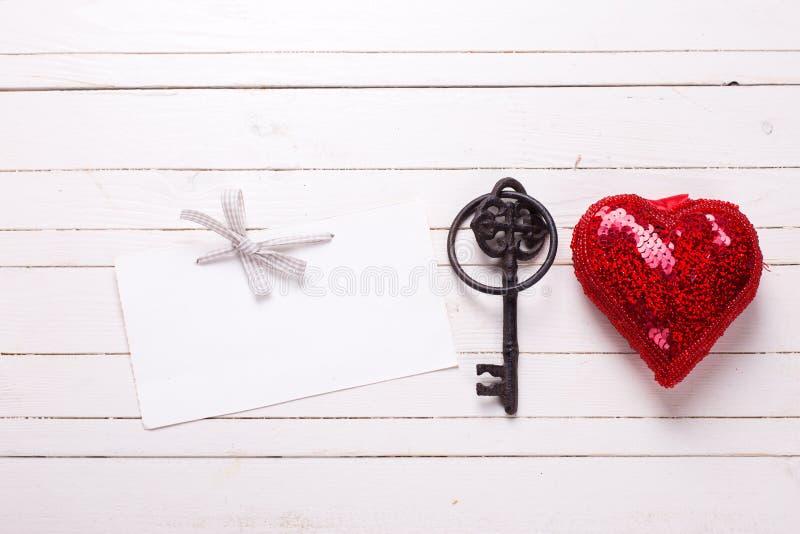 Rood decoratief hart, lege markering en sleutel op witte houten rug royalty-vrije stock foto's