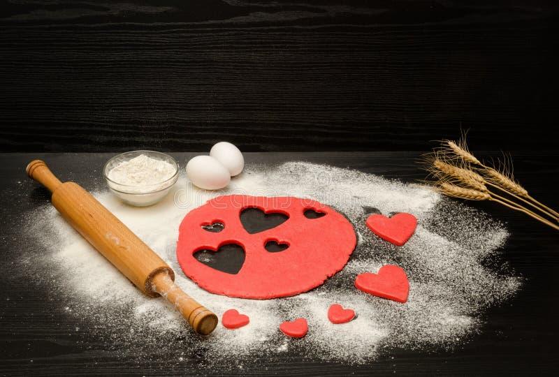 Rood deeg, verwijderde harten, bloem, eieren en deegrol op een zwarte achtergrond, oren van tarwe, ruimte voor tekst stock fotografie