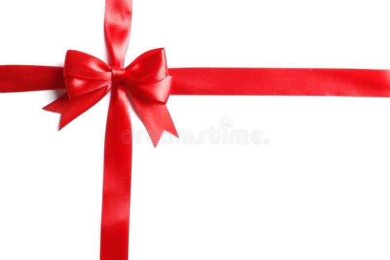 Rood die boog en lint op witte achtergrond wordt geïsoleerd stock afbeelding