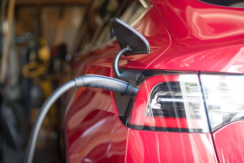 Rood die Elektrisch voertuig in Garage wordt gestopt royalty-vrije stock fotografie