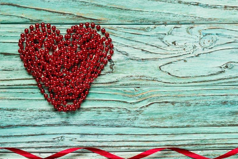 Rood die hart van parels op een houten turkooise achtergrond wordt opgestapeld Het bureau van C royalty-vrije stock afbeeldingen