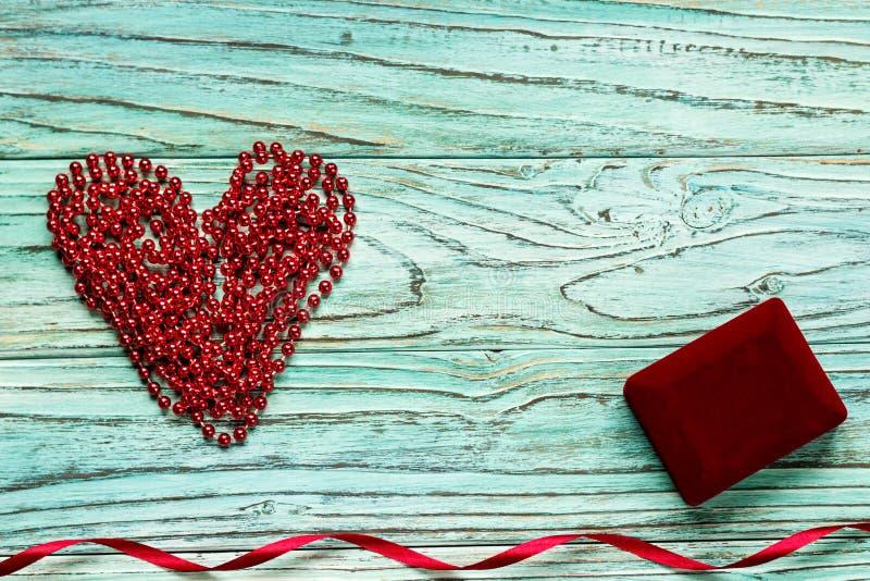 Rood die hart van parels op een houten turkooise achtergrond wordt opgestapeld Het bureau van C royalty-vrije stock foto's