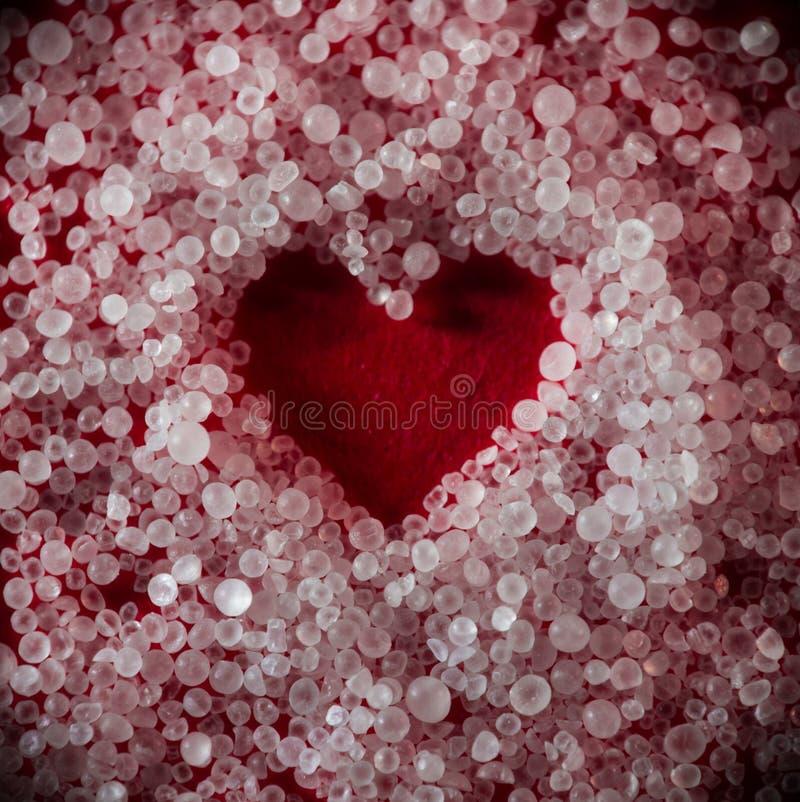 Rood die hart van ronde kleine zoute kristallen wordt gevormd royalty-vrije stock afbeelding