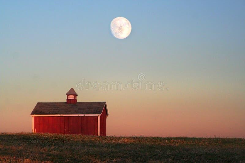 Rood die landbouwbedrijf met koepel boven op een heuvel met heldere volledige hierboven moonrise wordt afgeworpen stock foto's