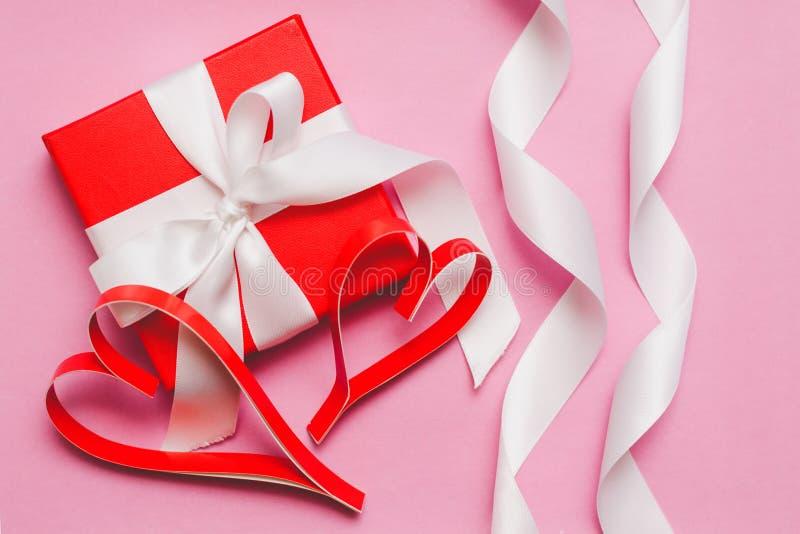 Rood die vakje met een gift, met een wit lint wordt gebonden, en rode eigengemaakte document harten op een roze achtergrond Symbo stock foto's