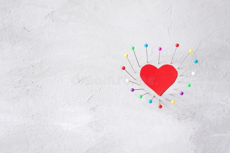 Rood document hart en naaiende spelden op grijze cementachtergrond Harde liefde, eenzaamheid, scheiding, verbrekenconcept stock afbeeldingen
