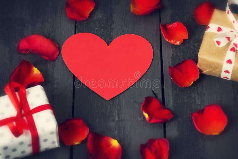 Rood document hart met roze bloemblaadjes en giften op een donkere houten achtergrond St de Dag van de valentijnskaart ` s stock foto