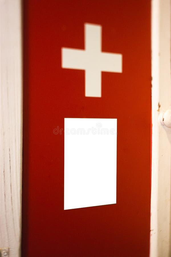 Rood eerste hulpkruis - Lichte vakje vertoning met witte lege ruimte voor reclame - Binnen stock foto