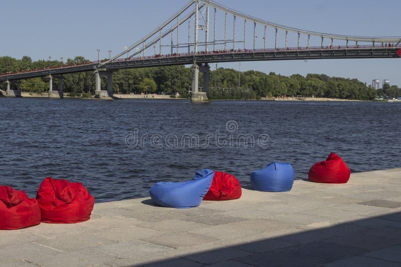 Rood en blauw strandkinderspel op de rivierbank Rust streek Over de rivierbrug stock foto's