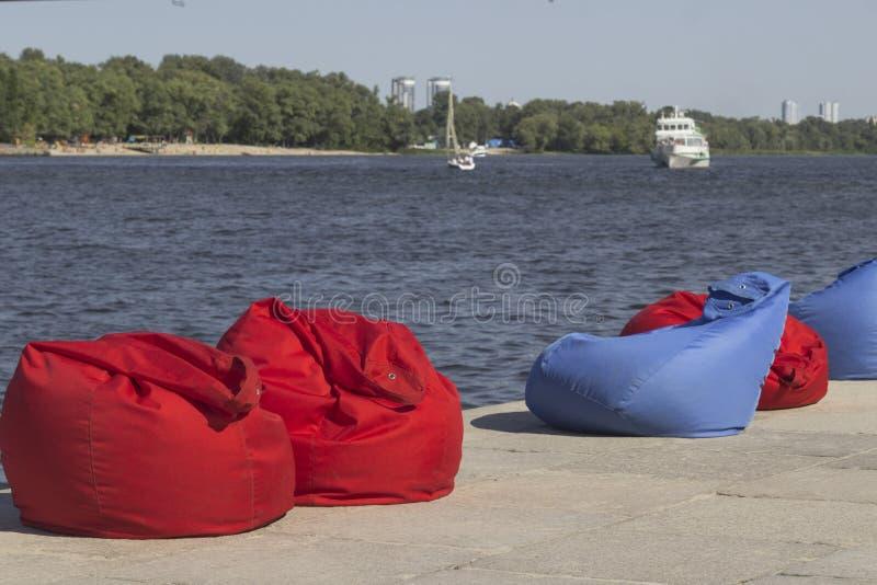 Rood en blauw strandkinderspel op de rivierbank Rust streek De schipzeilen langs de rivier stock fotografie