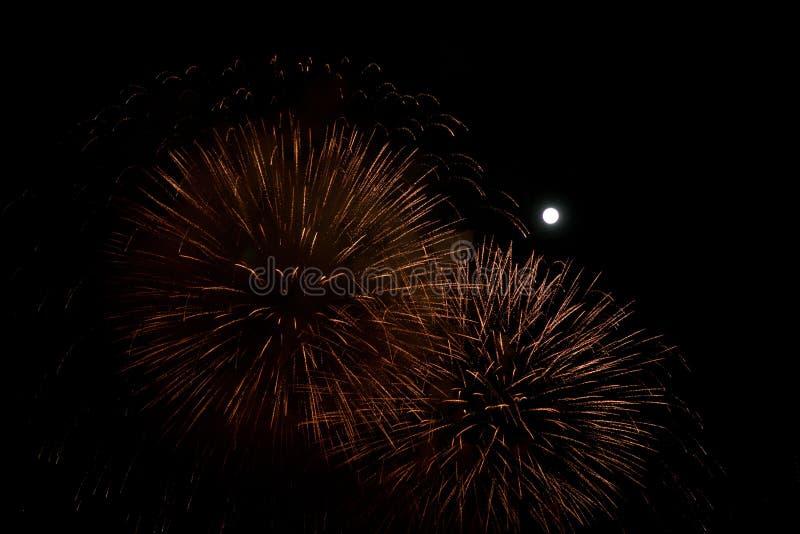 Rood en gouden vuurwerk bij nachtachtergrond met maan stock fotografie