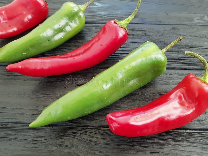 Rood en groene paprika het koele koken op een zwarte achtergrond stock afbeelding