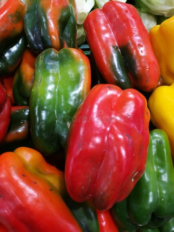 Rood en Groene paprika's bij landbouwersmarkt stock foto's
