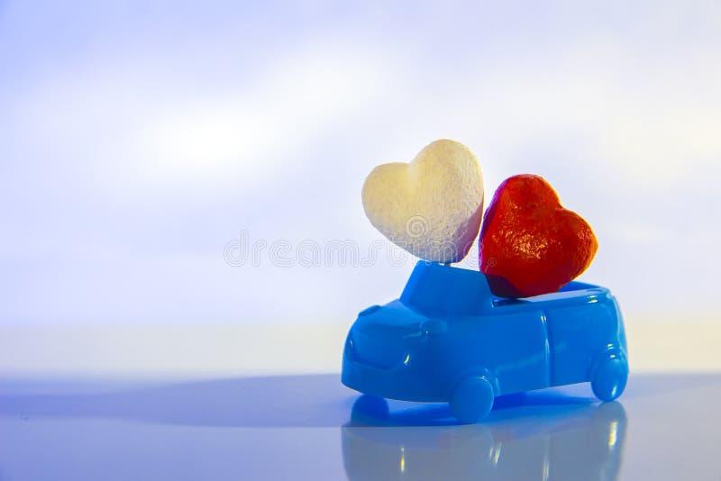 Rood en wit hart in een blauwe cabriolet auto op een lichte achtergrond Conceptenliefde en auto St Valentine ` s Dag voor royalty-vrije stock foto's