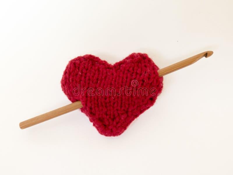Rood gebreid hart met een haak en een bal van wol stock afbeelding