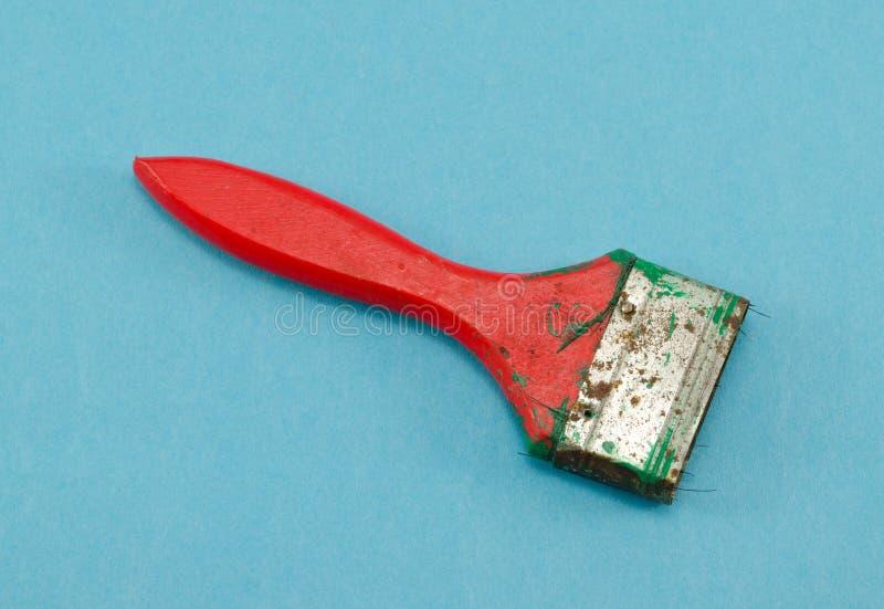 Rood gebroken het hulpmiddelhandvat van de verfborstel op blauw royalty-vrije stock afbeelding