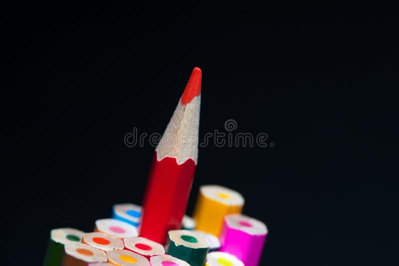 Rood gescherpt potlood onder kleurrijke kleurpotloden stock foto's