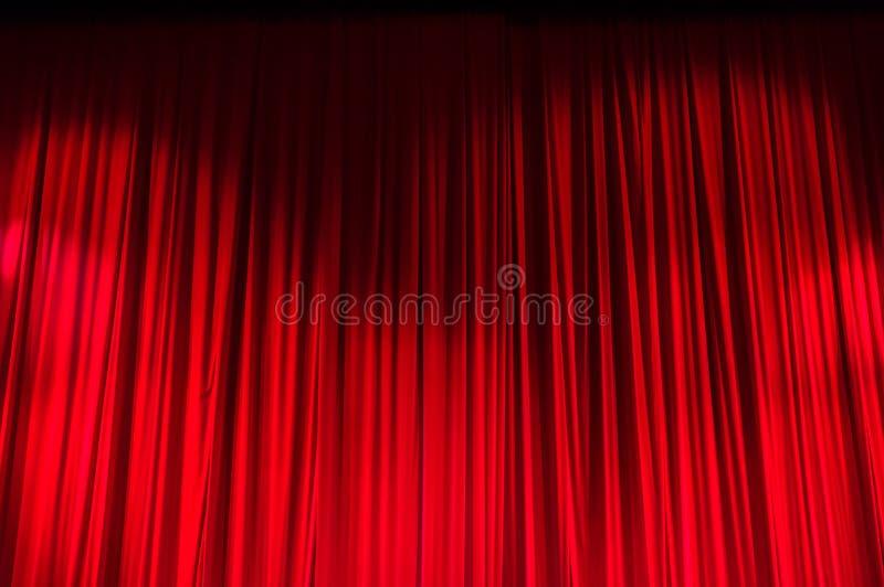 Rood gesloten gordijn met lichte vlekken in een theater stock foto's
