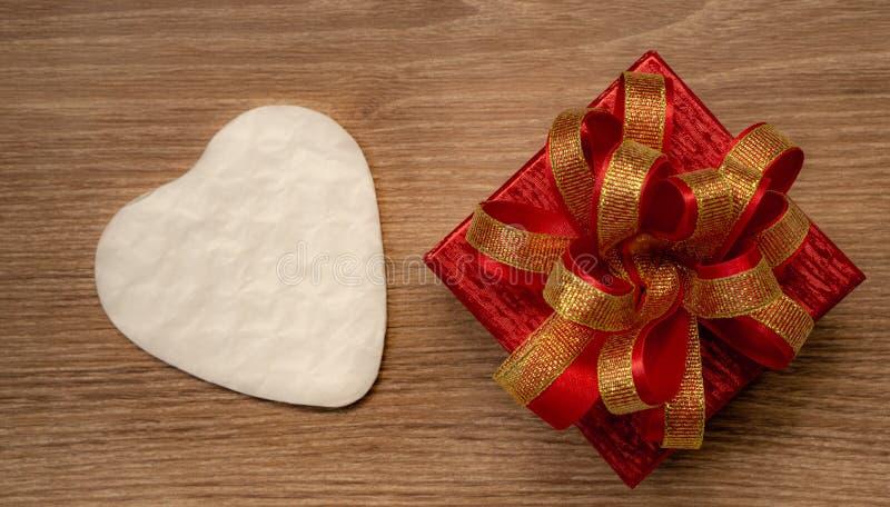 Rood giftvakje met gouden lint en wit die hartdocument voor de dag van verrassingsvalentijnskaarten huidig op bruine houten achte royalty-vrije stock afbeelding