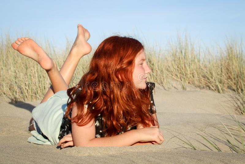 Rood haired meisje die op een wit zandig strand van Nieuw Zeeland liggen royalty-vrije stock afbeelding