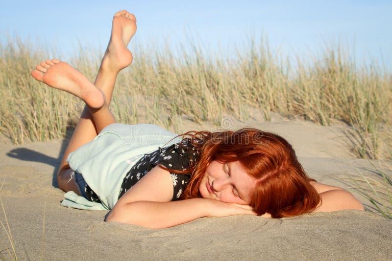 Rood haired meisje die op een wit zandig strand van Nieuw Zeeland liggen stock foto's