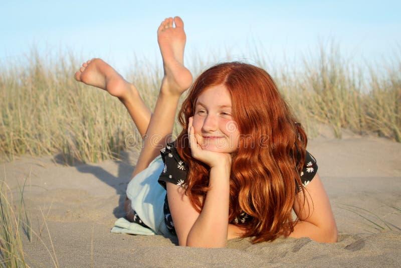 Rood haired meisje die op een wit zandig strand van Nieuw Zeeland liggen stock afbeelding