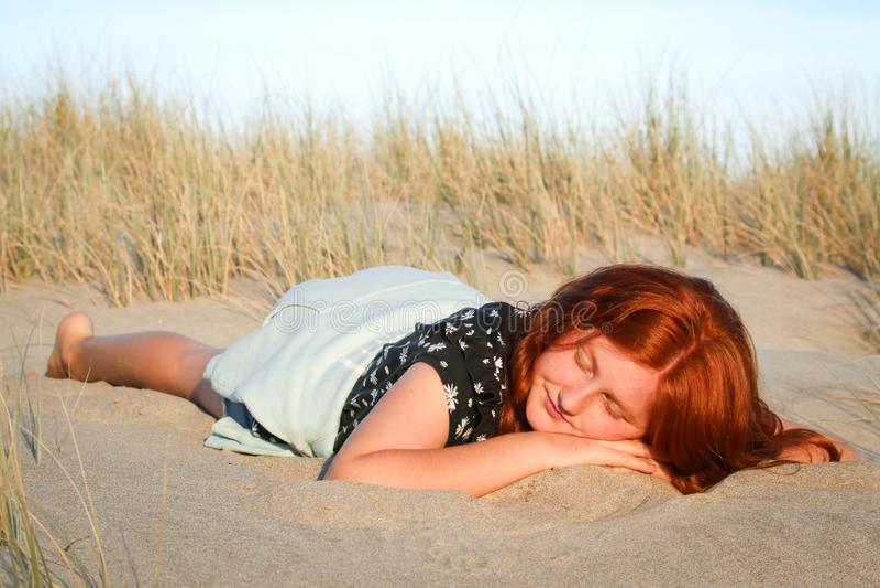 Rood haired meisje die op een wit zandig strand van Nieuw Zeeland liggen stock afbeeldingen